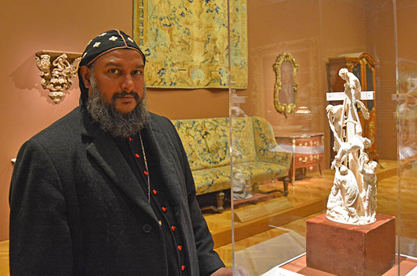 His Eminence Yeldo Mor Titus examining an ivory sculpture of Jesus' body being lowered from cross in Cleveland Museum of Art, Cleveland, Ohio